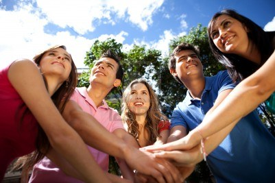 9600386-happy-team-of-people-with-hands-together-outdoors