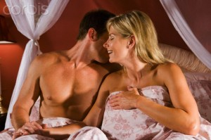 Romantic couple sitting up in bed under sheets holding hands