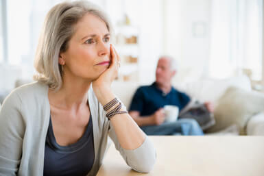 Senior woman unhappy, husband in background